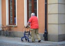 格但斯克波兰 老人有步行者支持沿街道去 免版税图库摄影