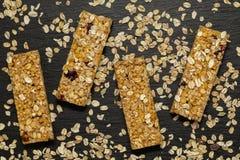 格兰诺拉麦片棒 健康甜点心快餐 谷物与坚果、果子和莓果的格兰诺拉麦片棒在一张黑石桌上 免版税库存图片