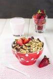 格兰诺拉麦片用草莓和酸奶在白色木背景 免版税库存照片