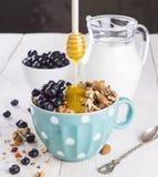 格兰诺拉麦片用蓝莓、薄菏、蜂蜜和牛奶在蓝色碗有牛奶罐的在一把白色桌和金属匙子 库存照片