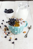 格兰诺拉麦片用蓝莓、蜂蜜和牛奶在蓝色碗在白色t 库存照片