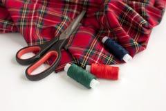 格子呢织品、剪刀和缝合针线 免版税图库摄影