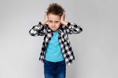 格子花呢上衣、蓝色衬衣和牛仔裤的一个英俊的男孩在灰色背景站立 男孩交叉他的在他的双臂 库存图片