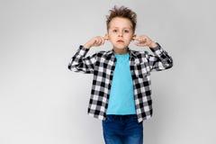 格子花呢上衣、蓝色衬衣和牛仔裤的一个英俊的男孩在灰色背景站立 男孩交叉他的在他的双臂 图库摄影
