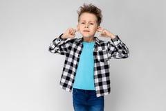 格子花呢上衣、蓝色衬衣和牛仔裤的一个英俊的男孩在灰色背景站立 男孩交叉他的在他的双臂 免版税库存照片