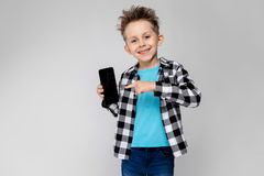 格子花呢上衣、蓝色衬衣和牛仔裤的一个英俊的男孩在灰色背景站立 男孩拿着一个电话 免版税库存照片