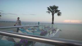 格子花呢上衣便衣的人慢慢地走在屋顶玻璃窗阳台的在美好的晚上日落海景 股票录像