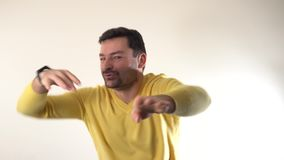 格子花呢上衣显示yo姿态用手的跳舞Hip Hop的可爱的成人有胡子的丈夫,站立反对灰色 股票录像