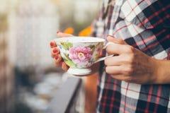格子花呢上衣的妇女喝在一个阳台的咖啡有城市视图 免版税库存图片