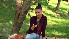 格子花呢上衣的年轻美丽的女孩坐一条长凳在公园,有效地重写在互联网闲谈 股票视频