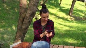 格子花呢上衣的年轻美丽的女孩坐一条长凳在公园,有效地重写在互联网闲谈 影视素材