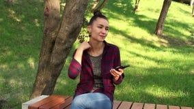 格子花呢上衣的年轻美丽的女孩坐一条长凳在公园,有效地重写在互联网闲谈 股票录像