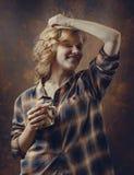 格子花呢上衣的年轻美丽的妇女有咖啡杯的 库存图片