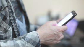 格子花呢上衣的时髦的年轻人使用一个智能手机 股票录像
