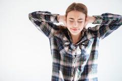 格子花呢上衣的皱眉的被注重的妇女用人工盖了耳朵 库存照片