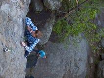 格子花呢上衣的英俊的人在岩石上升 免版税库存图片