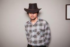 格子花呢上衣的年轻牛仔对绿色墙壁 免版税库存照片