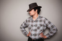 格子花呢上衣的年轻牛仔对绿色墙壁 库存图片