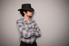 格子花呢上衣的年轻牛仔对绿色墙壁 免版税图库摄影