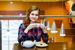 格子花呢上衣饮用的茶的体贴的女孩在caf 库存照片