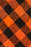 格子花呢披肩橙色和黑织地不很细背景样式 免版税库存图片
