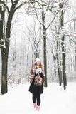 格子花呢披肩的一个女孩在冬天喝茶 免版税库存照片