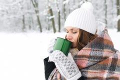 格子花呢披肩的一个女孩在冬天喝茶 库存照片