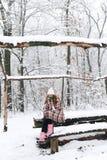 格子花呢披肩的一个女孩在冬天喝茶 库存图片