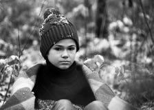 格子花呢披肩的一个男孩在雪走在单独秋天森林里我 库存图片