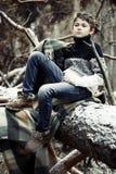 格子花呢披肩的一个男孩在雪走在单独秋天森林里我 库存照片