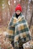 格子花呢披肩的一个男孩在雪走在单独秋天森林里我 免版税库存图片