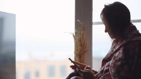 格子花呢披肩的沮丧的哀伤的妇女坐看在窗口的窗口基石,当使用手机时 1920x1080 影视素材