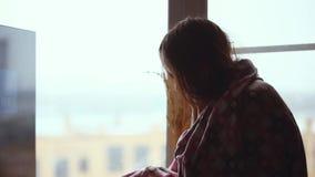 格子花呢披肩的沮丧的哀伤的妇女坐窗口基石 1920x1080 股票录像