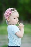格子花呢披肩盖帽的男婴在绿色背景 图库摄影