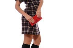 格子花呢披肩礼服的女孩有红色钱包的 免版税库存图片