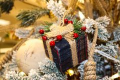 格子花呢披肩羊毛被包裹的圣诞节礼物装饰品栓与绳索和trimed用在一棵被聚集的土气圣诞树的莓果 免版税库存照片