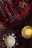 格子花呢披肩背包、咖啡和蜡烛 图库摄影