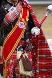 格子花呢披肩苏格兰男用短裙的吹笛者 库存图片