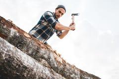 格子衬衫剁树的坚强的伐木工人在与锋利的轴的木头,接近轴,木片飞行 库存照片