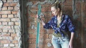 格子衬衫和蓝色牛仔裤的年轻苗条妇女以去的墙壁为背景做a的测量 股票录像