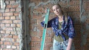 格子衬衫和蓝色牛仔裤的年轻苗条妇女以去的墙壁为背景做a的测量 影视素材