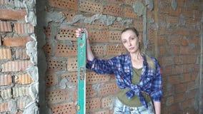 格子衬衫和蓝色牛仔裤的年轻苗条妇女以去的墙壁为背景做a的测量 股票视频