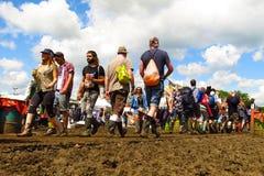 格拉斯顿伯里节日人群通过在晴朗的天空下的泥走 免版税图库摄影