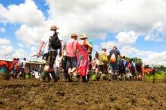 格拉斯顿伯里节日人群通过在晴朗的天空下的泥走 免版税库存图片