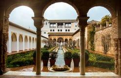 格拉纳达,西班牙- 2015年2月10日:露台的一个拱道有喷泉和cutted刷子的在阿尔罕布拉宫宫殿赫内拉利费宫庭院  库存图片