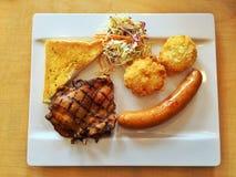 格栅与猪肉香肠集合的鸡牛排 库存图片