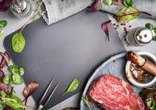 格栅在空白的黑板附近的牛排成份 格栅或用卤汁泡用烤肉汁的BBQ牛排 库存图片