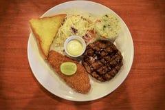 格栅猪肉和油煎的鱼排用沙拉、炒米和黄油面包在桌上 库存图片
