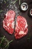 格栅, BBQ或者油煎的未加工的里脊肉牛排用草本和香料在土气金属背景,顶视图 库存图片