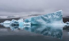 格陵兰,与完善的反射的蓝色冰山在充满天空的剧烈的心情的海湾 库存照片